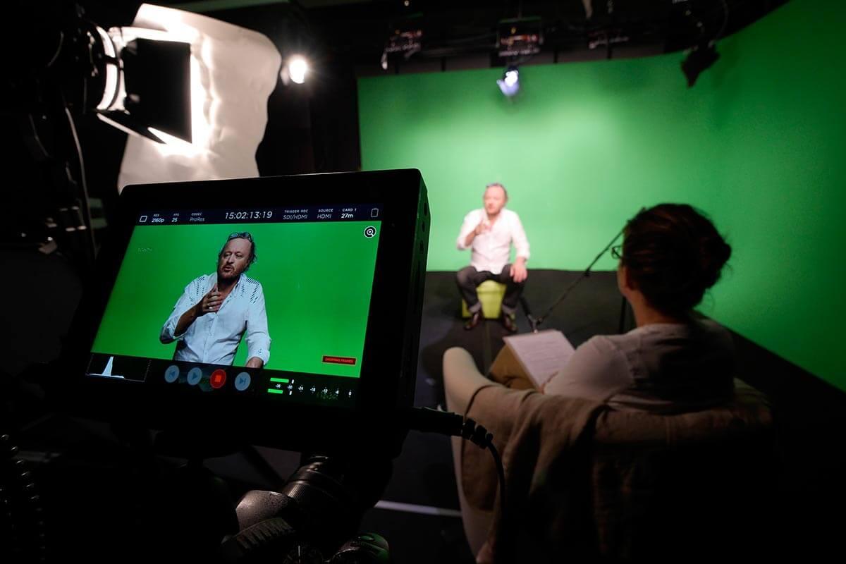 Le chef de projet Kronos Productions suit une captation audiovisuelle sur fond vert, en studio